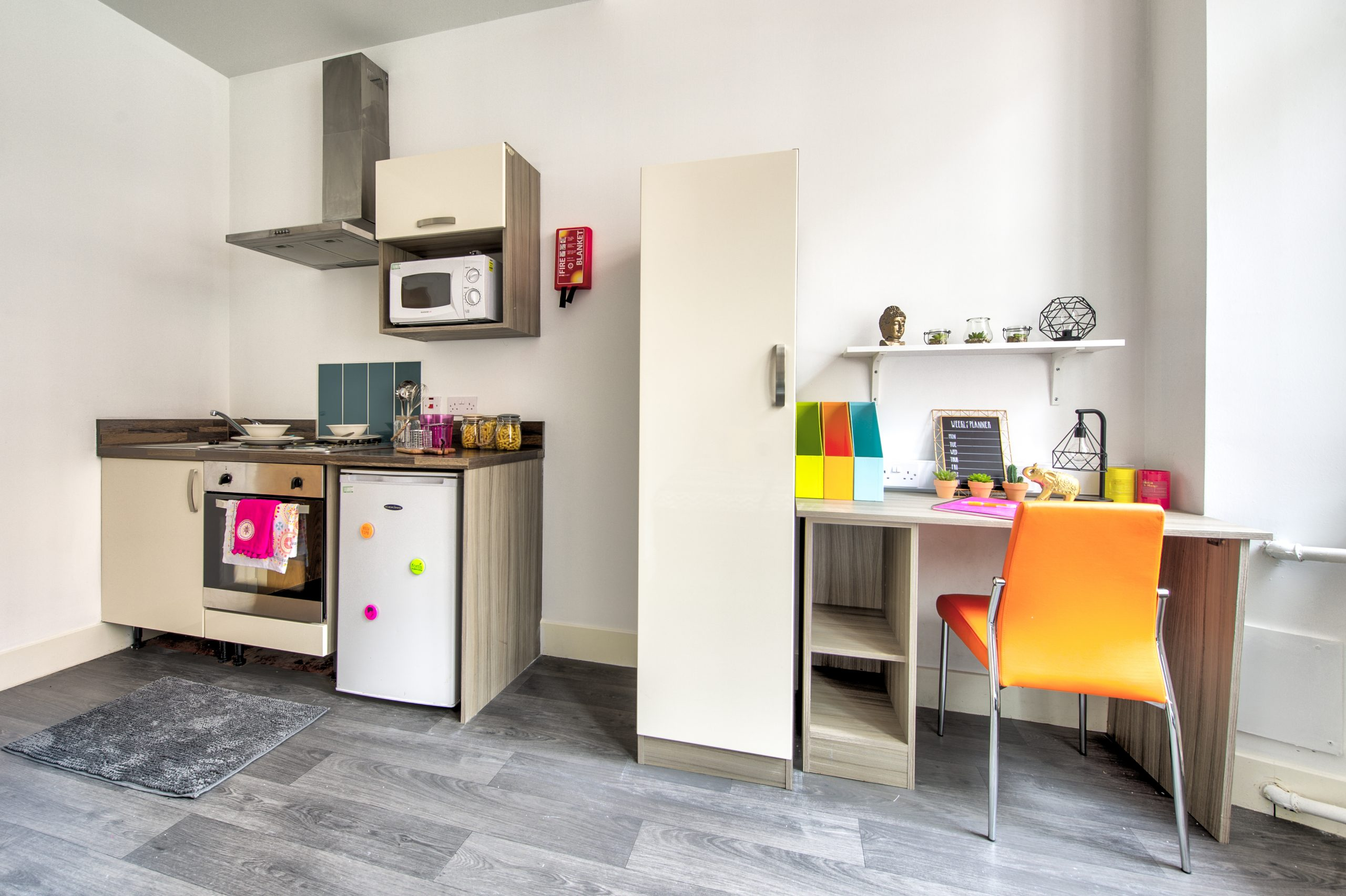 desk and kitchen area in studio apartment