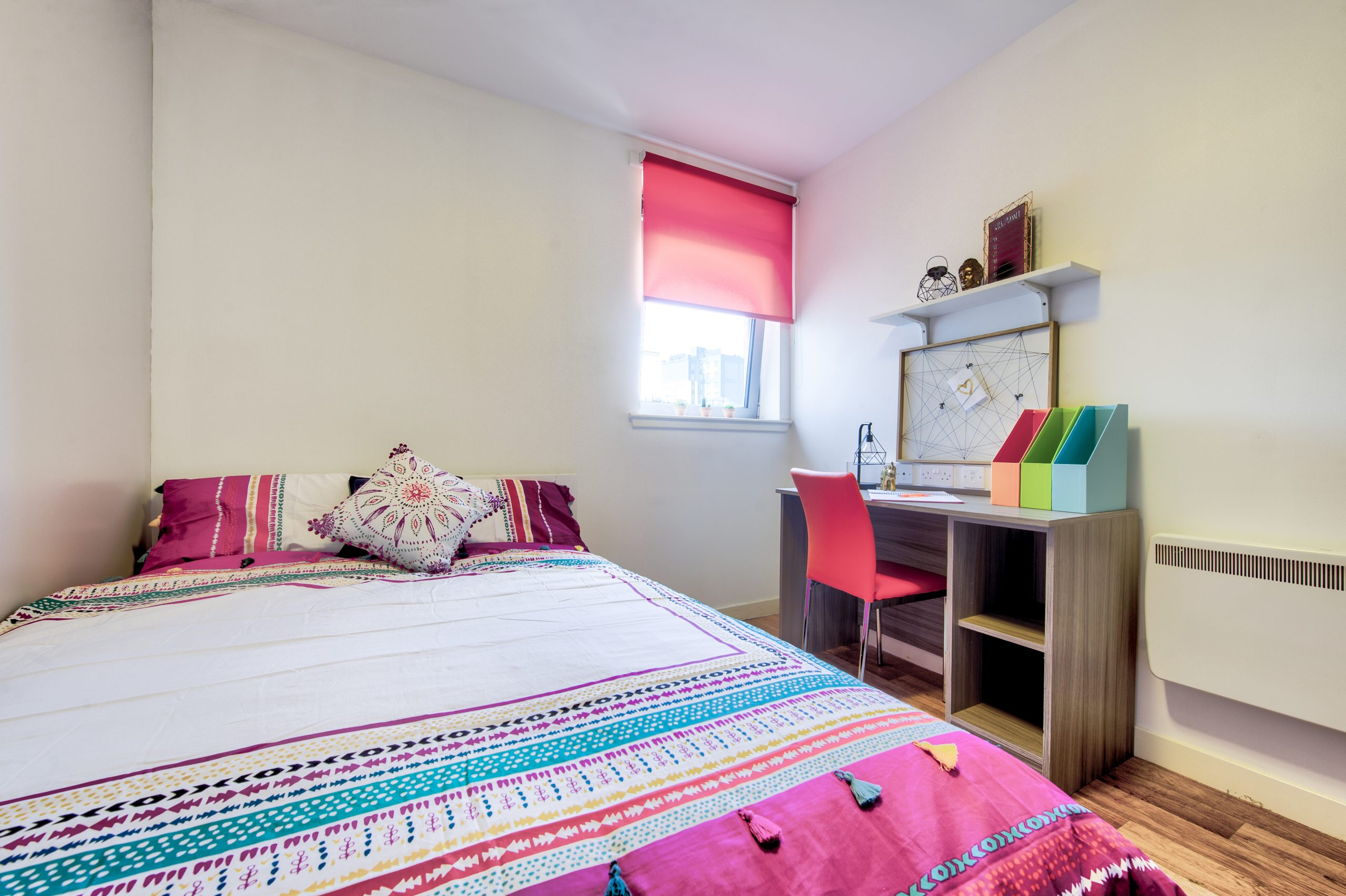 double bed and desk in student studio apartment