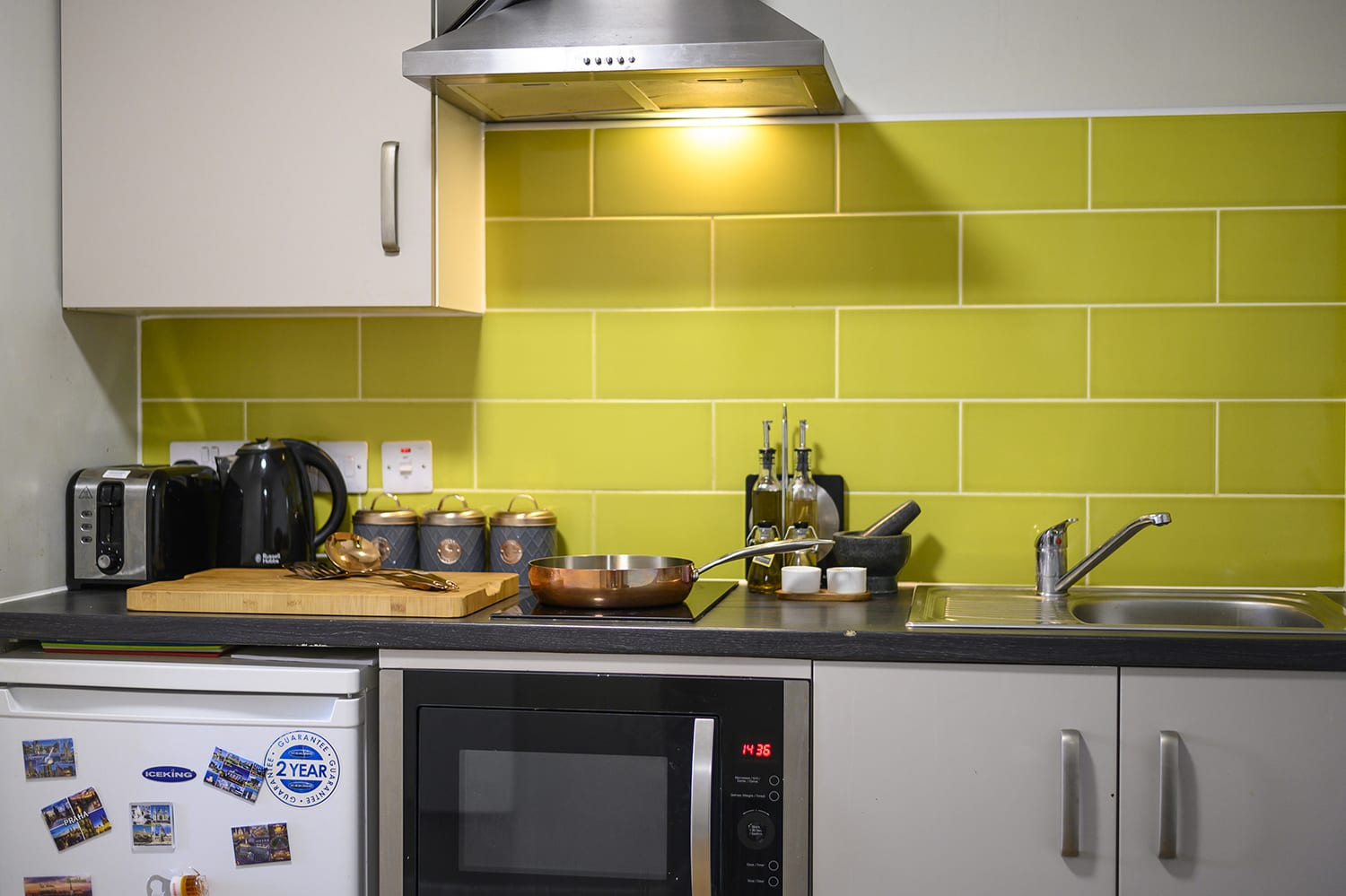 lime coloured tiled kitchen in student studio apartment